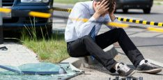 man-sitting-on-curb-after-car-accident-800x360